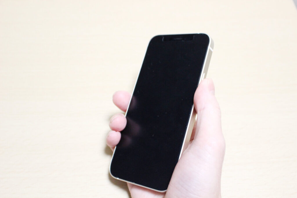 「iPhone12mini」を手に持つ
